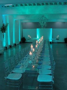Teal lighting with white candles and long glass table