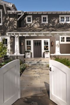Flanked by planters, windows and lanterns, this Craftsman entry couldn't be more inviting. I especially love the white and gray color palette.