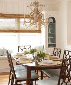 Going Coastal  A shell chandelier and sea-green cushions give a hint of beachy style without going overboard. A bamboo Roman shade is a great way to get coverage without blocking natural light.
