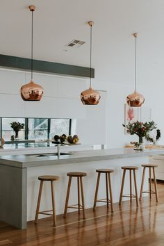 Modern kitchen with a concrete bench top and copper pendant lights. Designed by Studio Black Interiors