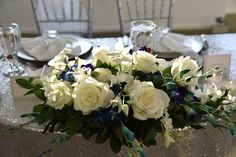 Floral spray for sweetheart table. Blue orchids, white roses, white orchids, hydrangea. Elegant, simple. Wedding reception. Silver table overlay