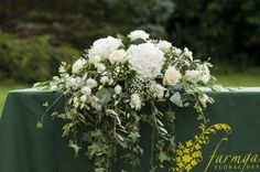 A flower arrangement for a wedding ceremony, suitable for a fireplace made up of white hydrangeas, white avalanche roses, white double eustoma and complimentary foliages of trails of ivy.