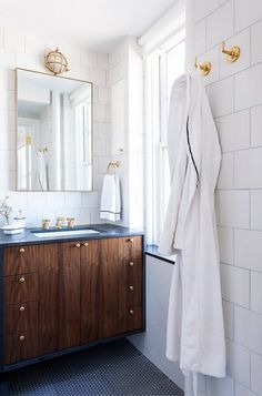 Clean and simple bathroom with a floating sink and a gold mirror