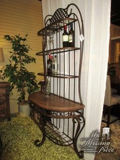 """Beautiful ornate bakers rack in a bronze finish. This bakers rack has two shelves as well as glass storage. Nice find for your kitchen or dining area! Measures 45""""wide x 19""""deep x 84""""high."""