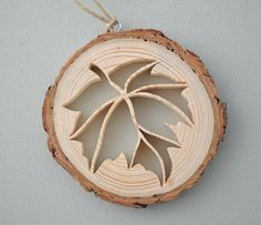Rustic Wood Leaf Ornament  The rustic wooden ornament depicts an open, lacy cutout of a leaf.  A slice of wood from the limb of a pine tree is the base for this unique ornament. The intricate picture was cut by hand, using a scroll saw. The bark is left on the wood, and the wood is unfinished for a very natural look.  The ornament is about 3 inches (7.6 cm) in diameter. It is just under 1/2 inch (13 mm) thick. The ornament hangs from a silver screw eye, hanging from a hemp cord.  This one of…