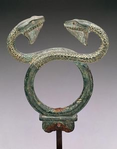 5th C. BCE. Upper part of a bronze caduceus,    snakes twined around a staff. Literally a 'herald.' Carried by Hermes, messenger of the Gods. Also, Hermes' Staff. Greece. Bronze,  5 x 4 1/8 x 3/4 in. Dallas Museum of Art