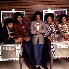 The Jackson 5 posing by two Bally pinball machines. Kick Off, and The Six Million Dollar Man.