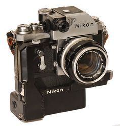 "Nikon F Camera with Motor 1959. Recognized by the round CdS cell on the front of the prism finder. The Photomic CdS meter prism read light directly through the meter, not through the lens. Nikon made 2 motordrives for the F camera. This was the press photographers camera with countless ""war"" stories about its toughness especially in the coverage of the Vietnam War."
