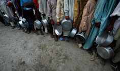 Flood victims holding their plates stand in queue for food handouts in Pakistan.