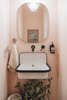 This townhome is a minimal, modern, monochromatic dream house with a pop of pink in its small bathroom. diy Dream house A Modern, Otherwise Monochrome Home Has a Precious Pink Guest Washroom