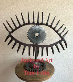 Junkyard Art by Tam-I-Am. Repurposed garden rakes and farm implement sprocket come together to make My Mind's Eye. Scrap metal art. #artsandcrafts
