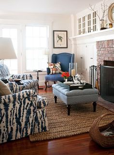 Blue upholstery punctuates this living space. Indigo tie-dyed fabric on the chairs is a nod to the mid-century - Traditional Home ®/ Photo: John Bessler / Design: Lisa Sternfeld