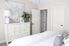 An elegant, serene master bedroom in white and gold