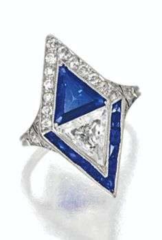 Diamond and sapphire ring, circa 1930. Centring a cut-cornered triangular-shaped diamond weighing approximately 1.60 carats and a cut-cornered triangular-shaped sapphire weighing approximately 2.10 carats in a lozenge shaped panel, framed by old European-cut diamonds and calibré-cut sapphires, mounted in platinum. #ArtDeco #ring
