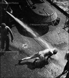 W. Eugene Smith  WORLD WAR II. The Pacific Campaign. 1943. From Pollywog to Shellback. A crew member being hosed aboard the USS Bunker Hill aircraft carrier (the ritual initiation when crossing the equator for the first time).