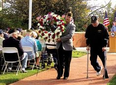 Clark Manley and Joseph Walters carry a wreath to place at Ocean City's war memorial at Veterans Memorial Park on Tuesday, in observance of Veterans Day.