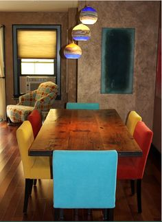 industrial modern dining table with italian design chairs with fun colored fabrics