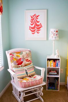 Adorable red & turquoise blue girl's nursery design with white rocking chair, blue walls paint color, bookcase, Good Shape Design Red Flock Print and lamp. white turquoise blue pink red nursery colors.