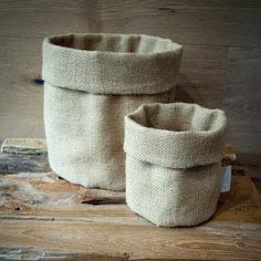 Fabric storage bags come in two sizes, and many colours. All bags feature a plastic lined base which protects against water damage, making them great for pot plants or for serving bread on the table. The uses for these little bags is unlimited. Approx Measurements: Small 12cm, Large 19cmProduct Fabric : Natural Hessian