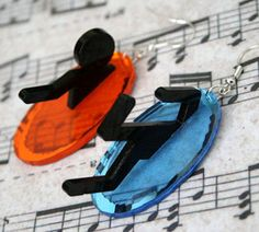 Portal earrings.  This pair of laser cut acrylic earrings, available on Etsy, is based on the game Portal. Each is made from mirrored blue and orange acrylic with a 3D black acrylic stick-man coming from, or going into, the front. They hang from silver plated earring wires and measure approximately 45mm from top to bottom.