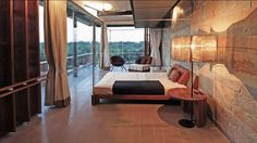 View of bed room with wooden bed and side unit with table lamp and wall with cladding work.