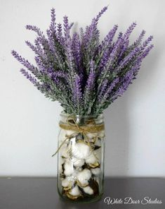 A cotton and lavender arrangement that oozes rustic charm. If farmhouse style is your thing, then this is a must have addition to your decor. Arrangement measures approximately 15H x 10W. Jar is 7H x 3W. Gorgeous faux lavender stems are secured in a cotton boll filled mason jar. Stems are secured