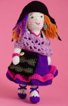 """A true multi-crafter who tries everything, Annie loves to """"make."""" She knits, crochets and gets inspired by new techniques. Crochet her from head to toe including her undergarments and shoes and then create her dress, mobius scarf and hat. Don't forget the creative touches—the purple streak in her hair, crocheted  project bag, bracelet and dangling earrings."""