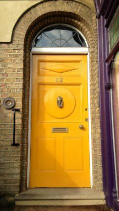 is that iron handle to the left of the door for? Very colorful, sunflower yellow door and eggplant purple window sashing . Cool Doors, Unique Doors, Portal, Knobs And Knockers, Door Knobs, Entrance Doors, Doorway, Grand Entrance, Yellow Front Doors