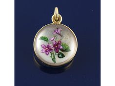 A 19th century reverse carved crystal pendant set in gold, depicting violets.