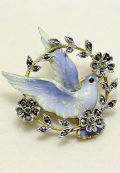 Enamel, diamond, ruby, gold and silver brooch, English or American, late 19th century-early 20th century. Designed as an enamel bird with a ruby eye perched on a rose-cut diamond wreath.