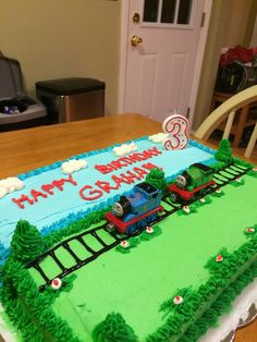 Thomas cake with buttercream icing & toy trains.