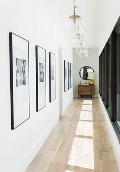 Pendant lights by Arteriors light a hallway, where an RH mirror hangs above a…