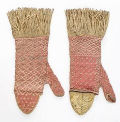 Pair of ladies' mittens, probably Italy, late 17th-early 18th century. Knitted fine rose-pink knitted silk with diapered and spotted patterns in gold and silver thread, the curved finger guard lined in lustrous gold braid, edged with gold fringes.
