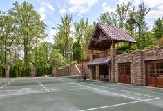 Enjoy a game or two of tennis at this rustic mountain retreat. There's even a shaded seating area for spectators. Outdoor Rooms, Outdoor Living, Infinity Edge Pool, Mountain Homes, Mountain Resort, Pool Houses, Estate Homes, Modern Rustic, Interior Architecture