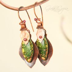 Hand cut copper leaves give an earthy backdrop for glowing green petals poking out from beneath copper loops.