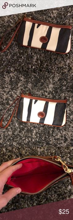 Dooney and Bourke clutch wallet Like new. Never worn just no tags. Handheld with wrist strap wallet/clutch  If you want to bundle anything else in my closet take a look! You'll get an additional discount on top of the 10% that's automatically taken off! I have tons of stuff!   🌸🌸🌸  Thanks for visiting! Dooney & Bourke Bags Clutches & Wristlets