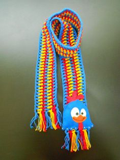 CACHECOL GALINHA PINTADINHA: em crochê com lã 100% acrílica.  Nas opções listrado ou liso (totalmente azul, por exemplo).  Aplique com motivo de Galinha Pintadinha em feltro.  Comprimento: 120 cm. R$ 55,00.