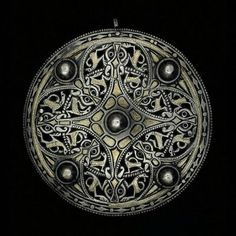 """artofthedarkages:  """"The Strickland Brooch"""" A circular brooch with deep cutting, decorated with sixteen small, doglike animals, eight animal heads with glass eyes, five bosses, and a beaded rim. The inlaid gold is unusually opulent for an Anglo-Saxon brooch. Crafted out of silver with inlayed gold, niello, and blue glass. Made in the 800s in Anglo-Saxon England. Acquired by antiquarian William Strickland in the 18th century and auctioned off in 1949 through Sotheby's to the British Museum…"""