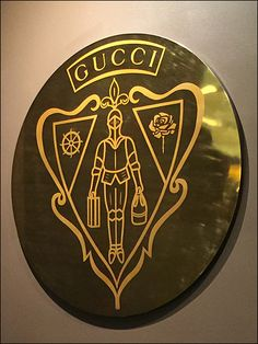Look close to see that this in-store Gucci® Coat of Arms embodies Leather Goods Luggage and Purse as part of the Heraldry.  It was difficult to discern if the Knight was in Flats or Kitten H...