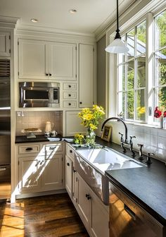 Off white, black hardware and counters. Cool sink. Big window. Wood floors. Details on the cabinet doors.