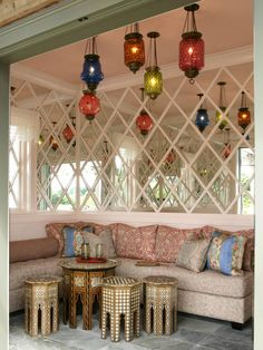 This colorful cabana features octagonal Moroccan side tables in various sizes and patterns, echoed overhead by an assortment of vibrant hanging lanterns.