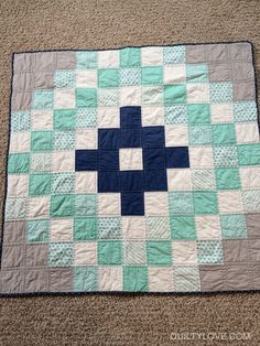 """This baby medallion quilt is super easyand uses charm packs. Charms are 5"""" square.This quilt uses an assortment of turquoise scrapsI had on hand along with a bella solid navy charm pack.I just layed out the pattern I wanted to make and sewedit together in rows."""