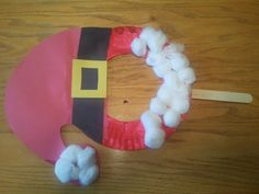 Santa or elf face mask made from a paper plate with paint, cotton balls, and construction paper.
