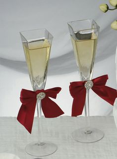 "These Red Allure Wedding Champagne Flutes feature stylish square toasting glasses trimmed with a charming red satin bow. A sparkling round charm finishes these beautiful glasses. Non-tarnish finish.Glasses measure 9.25"" tall"