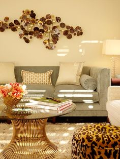 Chic living room design with butter yellow walls paint color, dove gray velvet sofa, Worlds Away Powell Cocktail table, shag rug, cheetah ottoman and bronze wall sculpture.