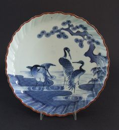 A Late 17th or Early 18th Century Japanese Blue and White Porcelain Dish Kakiemon Style, Arita Kilns c.1690-1720. Well Painted with Three Cranes (possibly red-crowned cranes) Near a Gnarled Pine Tree with Exposed Roots, there is Bamboo to the Right. The Cranes in Contrasting Positions Stand in Water that is Partly Rendered as a Brocade Pattern. The Thickly Potted Dish has a Scalloped Rim and Iron-oxide Dressing Referred to as Kuchibeni (literally meaning `lipstick`).