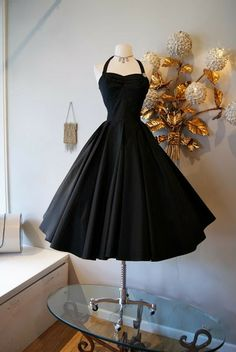 The ultimate little black dress! 1950's black taffeta with full circle skirt and halter neck. Simple yet spellbinding!