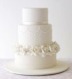 Bolo branco com textura de renda e gardênias de açúcar.