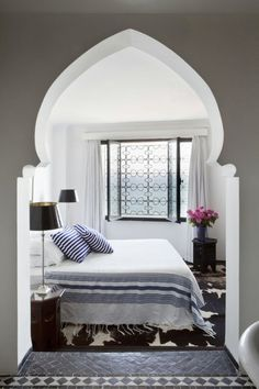 Airy Moroccan Bedroom -   The Moroccan style archway accents this beautiful, airy bedroom.  It's sleek and fresh theme includes  lively Moroccan floor tiles and a cowhide rug that provides great visual textures.  Source: Examiner
