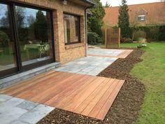"""Création d'une terrasse plus grande avec création de deux espaces : la terrasse en bois exotique contre l'habitation pour l'espace """"cosy"""" et une terrasse en pierre bleue avec entourage en bois pour le repas."""